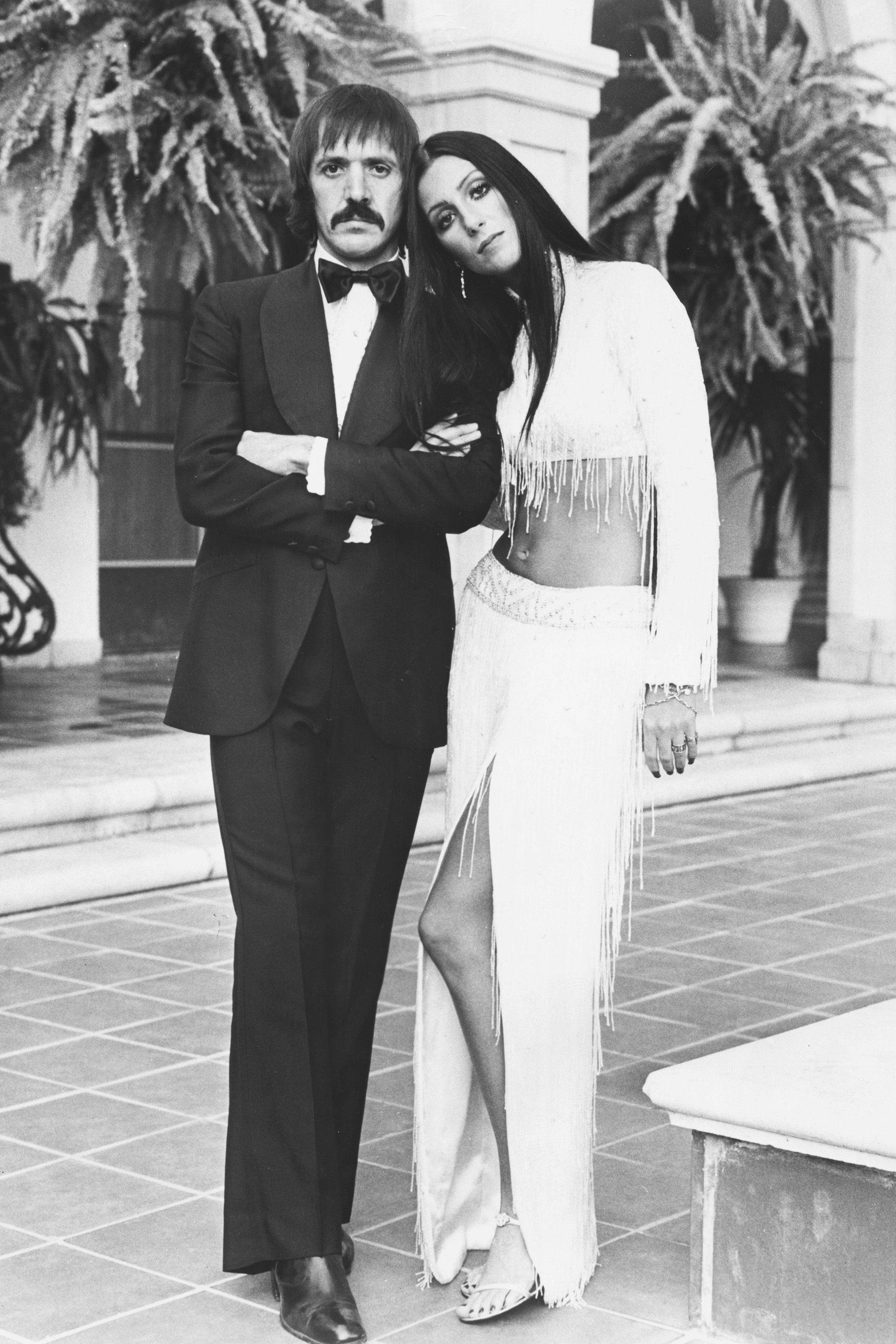 Portrait of singing duo Sonny Bono and Cher, wearing formal dress on an outdoor patio, circa 1975. (Photo by Archive Photos/Moviepix/Getty Images)