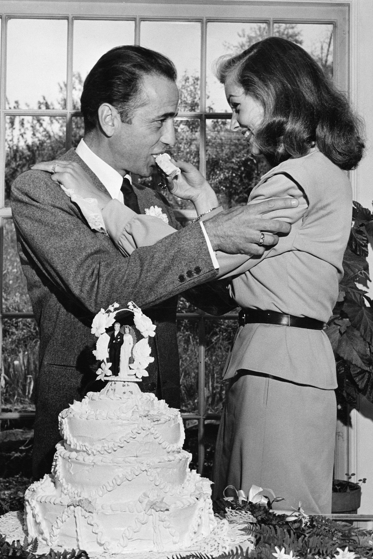 Actress Lauren Bacall feeding cake to husband Humphrey Bogart at their wedding at Louis Bromfield's farm.