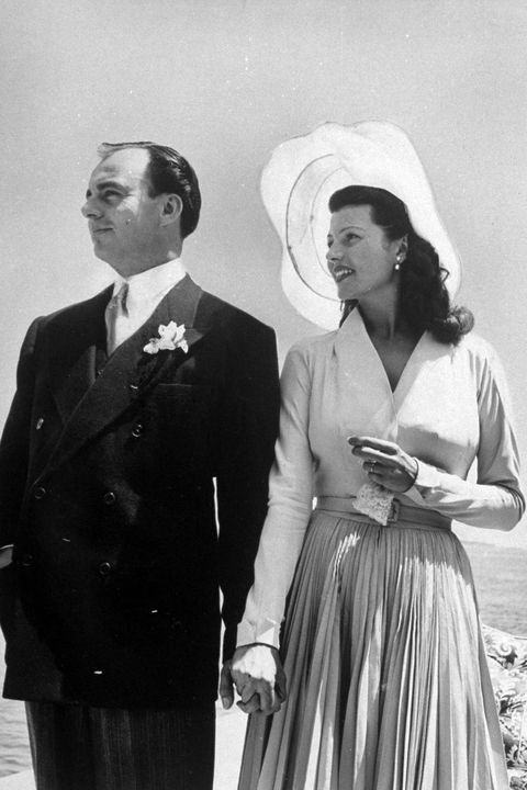 Prince Aly Khan w. his 2nd wife, actress, Rita Hayworth posing at seaside in their wedding clothes after ceremony, France.  (Photo by Nat Farbman/The LIFE Picture Collection/Getty Images)