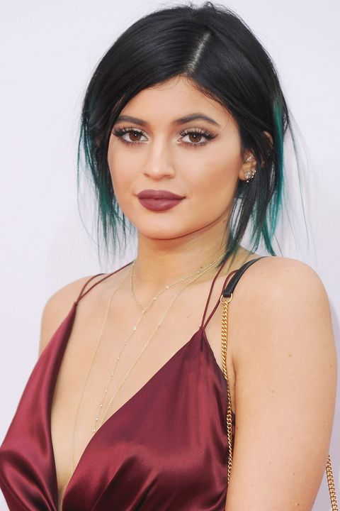 2014Berry lipstick and teal extensions pulled back into a messy bun in 2014.