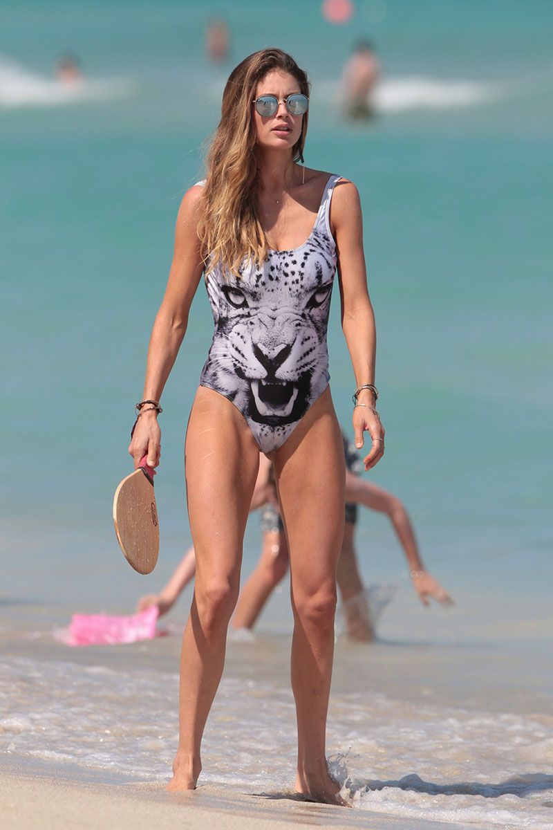 134910, Doutzen Kroes shows off her model figure as she plays paddle ball in a one piece bathing suit on the beach in Miami. The Dutch supermodel looked stunning in a silver one piece with the face of a snow leopard on it, as she played paddle ball with her friend. After the mother of two put her hair in a bun and cooled off in the ocean. Miami, Florida - Monday March 30, 2015. Photograph: Brett Kaffee/Thibault Monnier, © Pacific Coast News. Los Angeles Office: +1 310.822.0419 sales@pacificcoastnews.com FEE MUST BE AGREED PRIOR TO USAGE