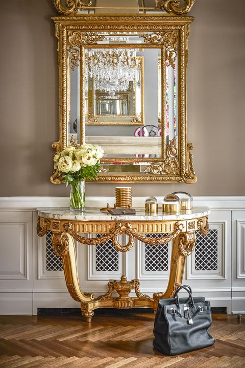 <p>McKee's front hallway clad with gold accents and a vintage Birkin bag. </p>