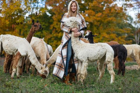 """<p><strong>HB: What inspired your to start Alicia Adams the collection?</strong><br></p><p><strong>AA:</strong> While I was a stay-at-home mom for our 3 young children, I supported Daniel with his alpaca breeding program, this included birthing crias (baby alpaca), training them for competitions and shows and helping during shearing day (once per year). The fiber was only a byproduct for us and it accumulated over the years. I was determined to do something with it. I didn't know much about fiber, knitting, weaving or anything in that field. But I did have a background in marketing and PR and a genuine interest in textiles and fashion. So I read many books, talked to knitters and weavers, went to fiber festivals and finally took the raw fiber to local mills to have it spun into yarn. After many attempts, I finally got back yarn that I considered luxurious and fine enough to launch a luxury collection. </p><p><strong>Joseph</strong> coat, $2,185,  <a href=""""http://www.joseph-fashion.com/coats/blanket-check-azha-coat/invt/w512708sh02060"""">joseph-fashion.com</a>&#x3B; <strong>Joseph</strong> sweater, $2,735, <a href=""""http://www.joseph-fashion.com/en/ecomus/womenswear/knitwear/icat/knitwear"""">joseph-fashion.com</a>&#x3B; <strong>Aquazzura</strong> boots, $995, <a href=""""http://www.net-a-porter.com/us/en/product/569804"""">net-a-porter.com</a>.</p>"""