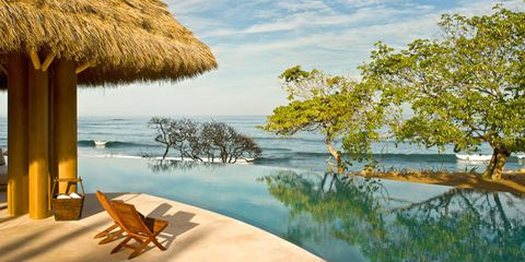 Body of water, Water, Natural landscape, Thatching, Outdoor furniture, Bank, Lake, Shore, Sunlounger, Shade,