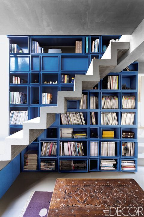 <p>Ino Caluza, owner of the custom-denim brand Viktor, looked to the work of Mexican architect Luis Barragán when designing his family home near Manila in the Philippines. The bright blue bookcase in the two-story library stands out against the concrete staircase and subdued furnishings.</p>