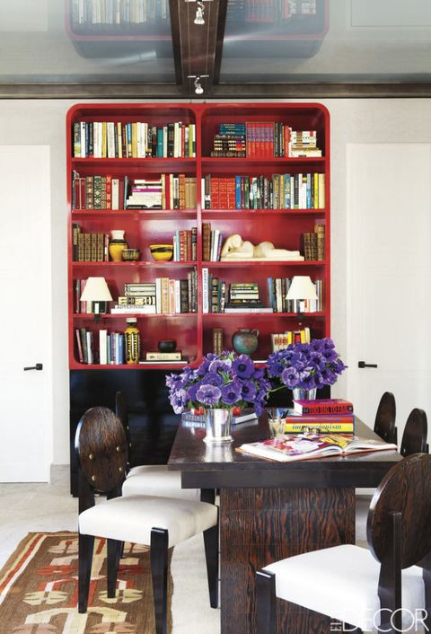"""<p>The library of a <a href=""""http://www.elledecor.com/design-decorate/room-ideas/g1440/bunny-williams-transforms-a-park-avenue-penthouse/"""" target=""""_blank"""">Manhattan penthouse designed by Bunny Williams</a> doubles as a guest room; a remote control-operated bed slides out from the base of the custom-made red-lacquered bookcase. The table and chairs are by André Sornay. </p>"""