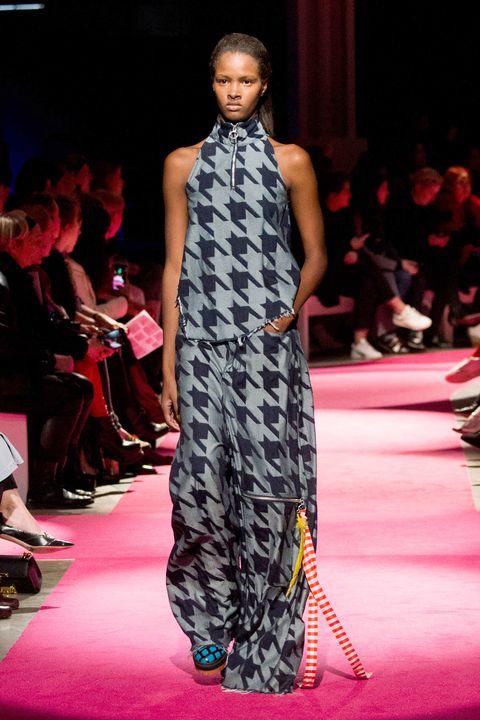 Fashion show, Shoulder, Outerwear, Dress, Runway, Flooring, Fashion model, Style, Carpet, Fashion,
