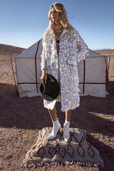 "<p><strong>Prada </strong>coat, $12,820, sweater-vest, $1,190, skirt, $5,280, and neckpiece, $525, <a href=""http://prada.com"" target=""_blank"">prada.com</a>; <strong>Satya Twena </strong>hat (worn throughout), $425, <a href=""http://satyatweena.com"" target=""_blank"">satyatweena.com</a>; <strong>Céline</strong> boots (worn throughout), $1,750, 212-420-7300. </p>"
