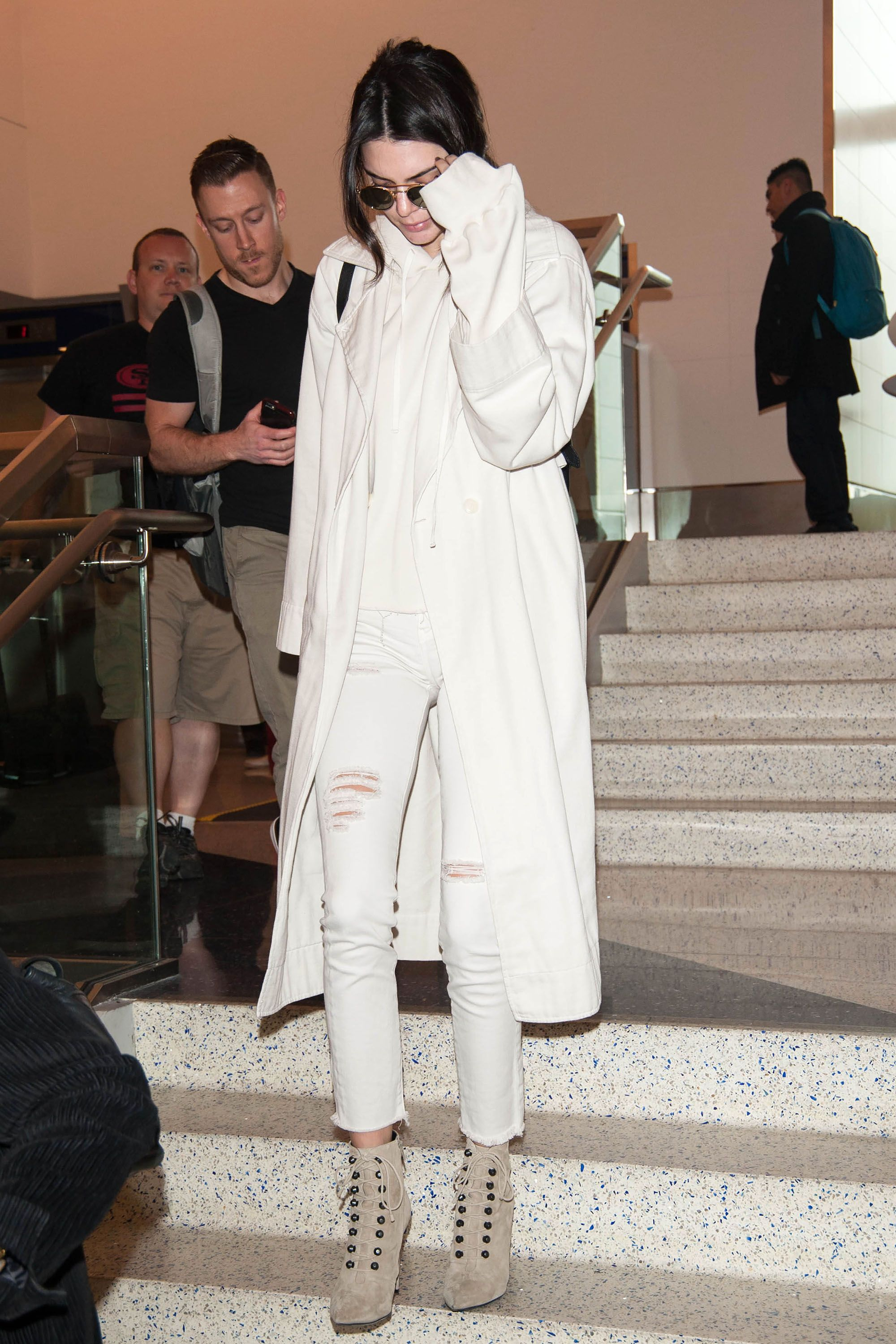 <p>Kendall Jenner covers her white jeans and top with a sweeping trench.</p>