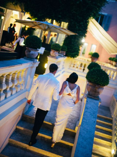 "<p>""We hosted two separate pre-wedding events: On Sunday night, there was a rehearsal dinner at <a href=""https://www.roccofortehotels.com/hotels-and-resorts/hotel-de-russie/restaurant-and-bar/le-jardin-de-russie/"" target=""_blank"">Le Jardin de Russie</a>. It was a formal event with speeches and the guest list was comprised of only family and the bridal party–an intimate setting was the best occasion to introduce my Italian family to Philip's extended one. The evening started outside on the balcony for aperitifs and then we moved into the dining room for a formal Italian meal. My vision for our rehearsal dinner aimed for a mid-century Dolce Vita vibe, and when I saw this traditional cowl-necked bow dress at Valentino, it seemed like the right fit. </p><p>The next evening, we hosted a more casual welcome dinner for all of the invited guests at <a href=""http://www.pierluigi.it/"" target=""_blank"">Ristorante Pierluigi</a>. We ate in the Piazza outside and enjoyed champagne and passed hors d'oeuvres, followed by a plated meal of traditional seafood dishes like <i>insalata catalana</i>. Even though it was a seated dinner, people could move around freely and get to know each other in a more convivial setting."" </p>"