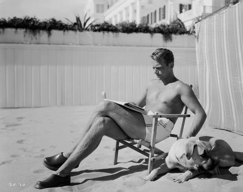 "<p>Actor Douglas Fairbanks Junior lounges bare-chested on a deckchair on the beach in Los Angeles, California.<br></p><p>Other celebrity visitors this year: actress Toby Wing, Shirley Temple.<span class=""redactor-invisible-space""></span></p>"