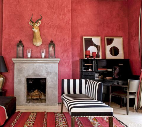 "<p>In a <a href=""http://www.elledecor.com/home-remodeling-renovating/home-makeovers/g1060/morrocan-house-studio-ko/"" target=""_blank"">Moroccan vacation home</a>, the salon walls are coated with a striking red stucco and a taxidermy antelope hangs above a fireplace covered in <em data-redactor-tag=""em"">tadelakt,</em> a traditional Moroccan plaster technique. The chaise is upholstered in a striped fabric from Toiles de Mayenne, and silk-screened prints by Gerhard Doehler sit above the desk.</p>"