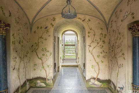 <p>For the entrance hall of a 17th-century farmhouse on the border of Italy's Tuscany and Umbria regions, designer Eric Egan commissioned Florentine decorative painter Francesca Guicciardini to create a whimsical mural of birds and botanicals. The tole light fixture is custom made, and the flooring is terrazzo.</p>