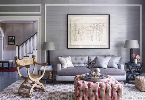 "<p>For a <a href=""http://www.elledecor.com/design-decorate/house-interiors/g440/thom-filicia-connecticut-home/"" target=""_blank"">weekend home in Greenwich, Connecticut</a>, designer <a href=""http://www.thomfilicia.com"" target=""_blank"">Thom Filicia</a> sheathed the family room walls in a grass cloth by <a href=""https://www.phillipjeffries.com"" target=""_blank"">Phillip Jeffries</a> and custom designed the sofa in complementary fabrics. The custom ottoman is upholstered in a <a href=""http://www.kravet.com/products/carpets/"" target=""_blank"">Kravet</a> wool, the lamps are by <a href=""http://www.luccaantiques.com/item/grid/1/2/"" target=""_blank"">Lucca Studio</a> and the round iron side table is from <a href=""https://www.lillianaugust.com"" target=""_blank"">Lillian August</a>.</p>"