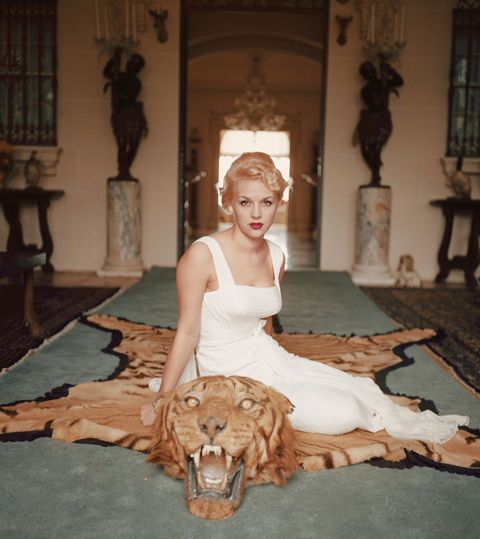 "<p>Lady Daphne Cameron sits on a tiger pelt in the trophy room of Laddie Sanford's Palm Beach house.<span class=""redactor-invisible-space"" data-verified=""redactor"" data-redactor-tag=""span"" data-redactor-class=""redactor-invisible-space""></span></p>"