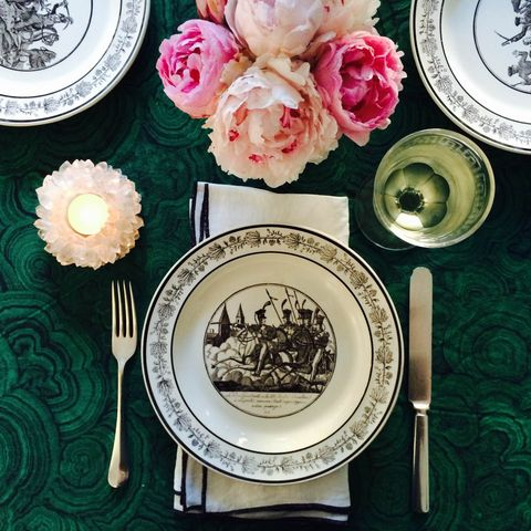 """<p>And in focusing on the table, feel free to deviate from the standard red-and-green. """"Rather than the traditional red and green scheme, try something new like a fabric in malachite and hot pink peonies,"""" says designer <a href=""""http://grantkgibson.com"""" target=""""_blank"""">Grant Gibson</a>. """"Layer in black and white for a graphic pop. The plates [here] are antique French.""""</p>"""