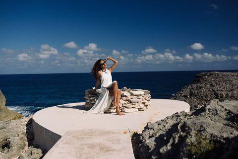 Sky, Coastal and oceanic landforms, Dress, Elbow, Summer, Rock, Vacation, Ocean, Sea, Bedrock,