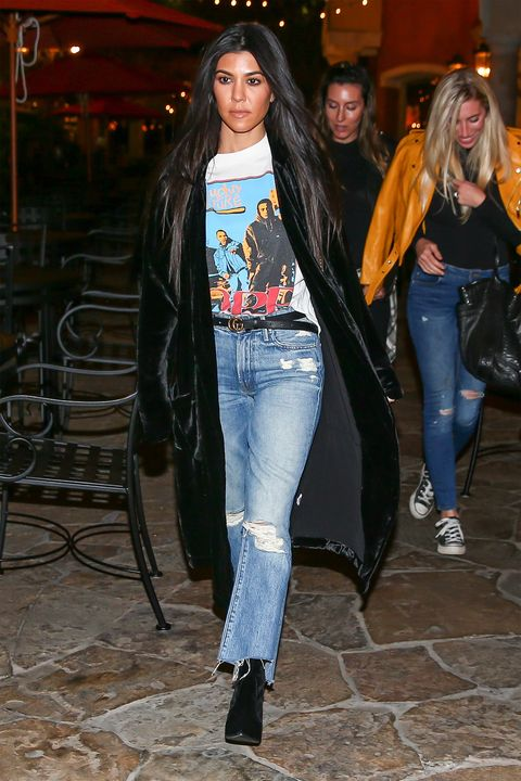 463aa16ac883 Kourtney Kardashian prefers rocker chic in cropped jeans, band tee and a  sweeping velvet cardigan.