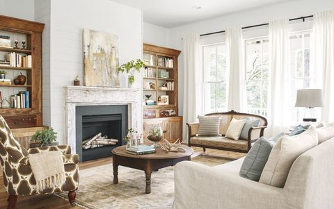 """<p>A mix of vintage and catalog finds lends a casual vibe in <a href=""""http://www.countryliving.com/home-design/house-tours/g3208/southern-georgia-farmhouse/"""" target=""""_blank"""" data-tracking-id=""""recirc-text-link"""">this Georgia farmhouse's</a>living room, where pine bookcases, rescued from a demolished elementary school, keep company with a new linen sofa. An abstract painting by artist —and<em data-redactor-tag=""""em"""">CL</em>General Store vendor—<a href=""""http://www.deanndesigns.com/"""" target=""""_blank"""">Deann Hebert</a>adds texture above the chippy mantel.<span class=""""redactor-invisible-space"""" data-verified=""""redactor"""" data-redactor-tag=""""span"""" data-redactor-class=""""redactor-invisible-space""""></span></p>"""