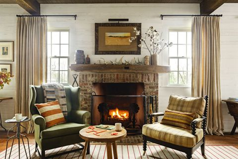 """<p>A wingback chair and a spindle chair give <a href=""""http://www.countryliving.com/home-design/house-tours/g3687/beechwood-farm-debra-koehler/?slide=1"""" target=""""_blank"""" data-tracking-id=""""recirc-text-link"""">this Alabama dogtrot home</a>'s living ri a collected-over-time vibe. The rustic mantel makes things feel extra rustic.</p>"""