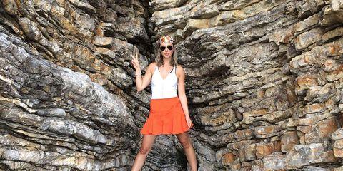 Rock, Human leg, Sunglasses, Bedrock, Beauty, Street fashion, Sleeveless shirt, Knee, Outcrop, Formation,
