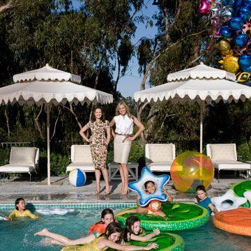 elizabeth wiatt and jamie tisch stand near a pool filled with children