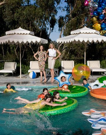 elizabeth wiatt and jamie tisch stand near a pool filled with children