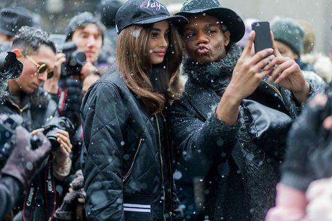 People, Jacket, Hand, Winter, Cap, Hat, Street fashion, Leather jacket, Leather, Baseball cap,