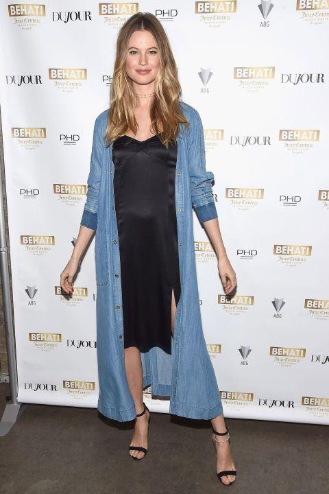 <p>De zwangere Behati Prinsloo leukte haar zwarte jurkje op met een lange jas van spijkerstof van haar eigen collectie voor Juicy Couture.</p>