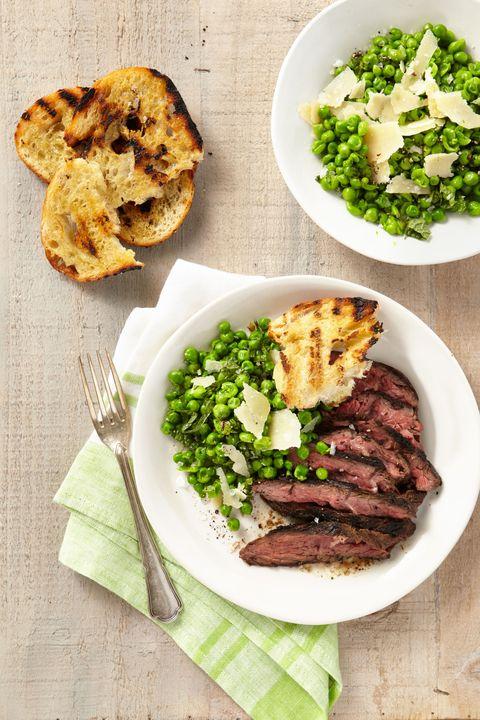 "<p>Geef een traditionele steak een frisse twist met erwten en parmezaanse kaas. </p><p><a href=""http://www.countryliving.com/food-drinks/recipes/a37762/grilled-cumin-rubbed-hanger-steak-smashed-minty-peas-grilled-bread-recipe/"">Het volledige recept vind je hier.</a></p>"