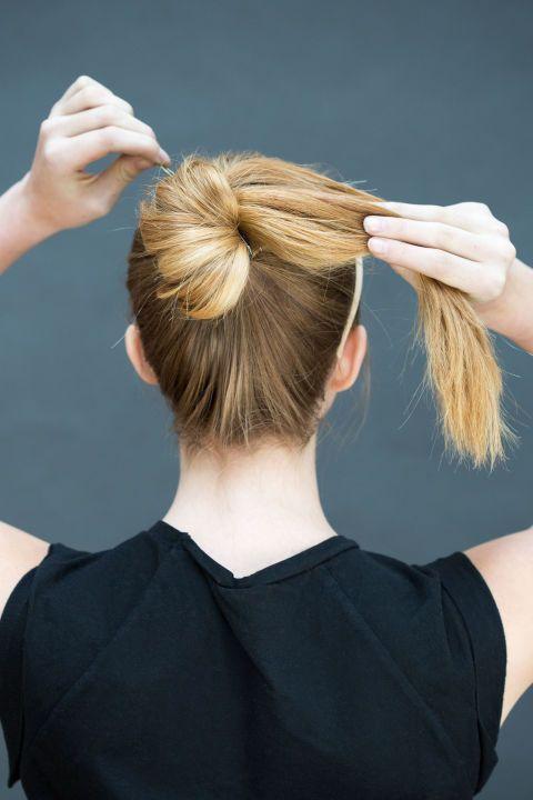 <p>Maak van je staart een knot, door het haar langzaam één kant op te draaien, en zet het vast met een elastiekje of schuifspeldjes</p>