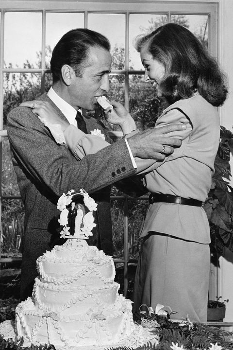 Actress Lauren Bacall feeding cake to husband Humphrey Bogart at their wedding at Louis Bromfield's farm.