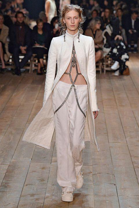 <p>Ook in de collectie van modehuis Alexander McQueen mocht wit niet ontbreken. Sarah Burton liet zich inspireren door de Londense zijdewevers uit de 17e eeuw maar gaf er een moderne draai aan door veel grote sieraden, net als deze body chain tot over de heupen. </p>