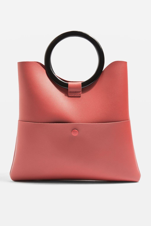 "<p>Handtas van imitatieleer, € 29,00 <strong data-redactor-tag=""strong"" data-verified=""redactor"">Topshop</strong> via <a href=""http://eu.topshop.com/en/tseu/product/bags-accessories-1702217/bags-purses-485127/cookie-o-ring-clutch-bag-6915172?bi=0&ps=20"" data-tracking-id=""recirc-text-link"" target=""_blank"">topshop.com</a><span class=""redactor-invisible-space"" data-verified=""redactor"" data-redactor-tag=""span"" data-redactor-class=""redactor-invisible-space""></span></p>"