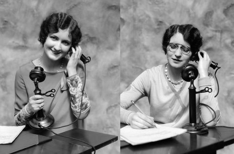 1920s WOMAN WEARING PINCE-NEZ GLASSES SITTING AT DESK TALKING ON CANDLESTICK PHONE AND WRITING  (Photo by H. Armstrong Roberts/ClassicStock/Getty Images)