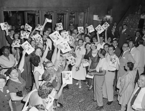 Actress Joan Crawford is surrounded by fans as she hands out autographed photographs of herself to early arrivals at the premiere of her film Sudden Fear, in the lobby of Loew's State Theatre in New York City.