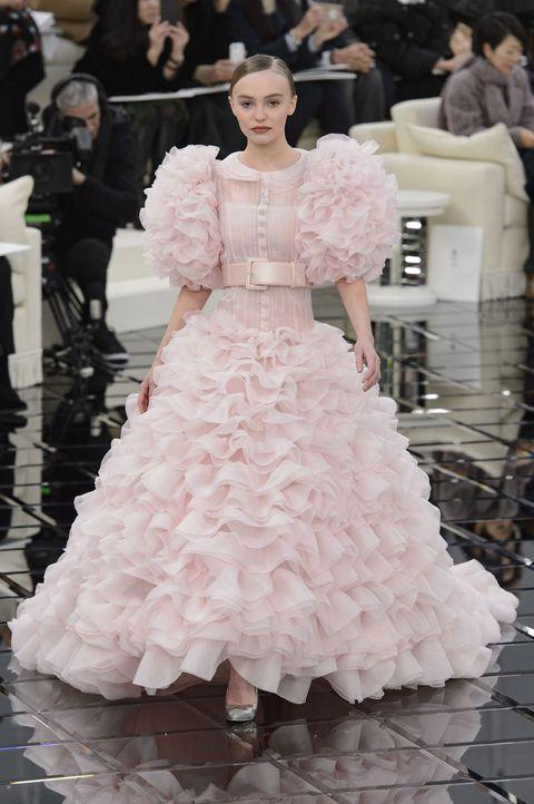 <p>正如粉紅玫瑰所代表的意涵:感動、宣誓、永遠的愛;在無比重要的婚禮上,選擇如夢似幻的粉色婚紗,讓幸福在穿上禮服的那刻永遠跟隨,也讓平時抑制已久的少女心,在這特別的日子無限萌發。</p><p>層次豐富的的荷葉設計與淡淡粉色,交融出無與倫比的浪漫意象,在搶眼蓬鬆的輪廓上,繫上寬版腰帶,顯出曲線,使得踏出的每個步伐,都如點水般輕盈夢幻。</p><p>Chanel 2017春夏高訂系列。</p>