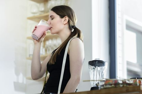 Woman drinking a meal replacement shakes. Horizontal shot.