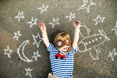 Portrait of smiling toddler wearing pilot hat and goggles lying on asphalt painted with airplane, moon and stars