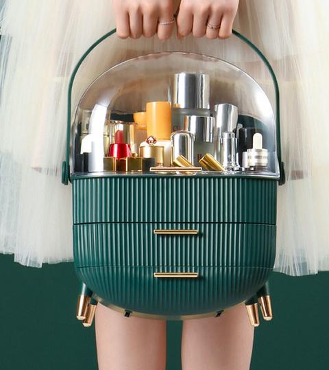 一個穿著白色蕾絲群的女生拿著綠色的手提化妝箱