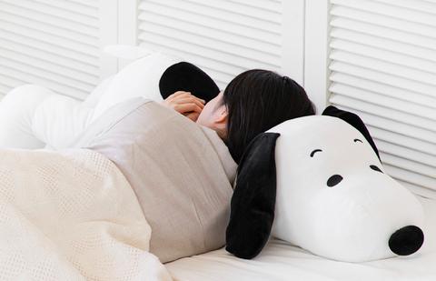 一個女生穿著灰色睡衣趴在史努比玩偶上