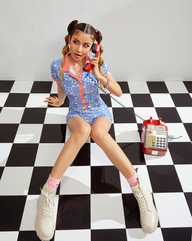 woman in blue playsuit talking on the phone