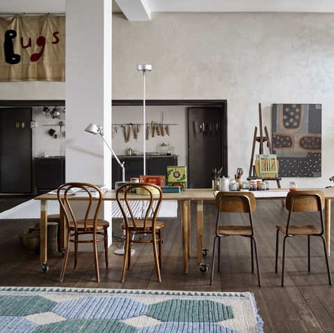 vintage wooden table and mismatched chairs in the dining room of this creative home