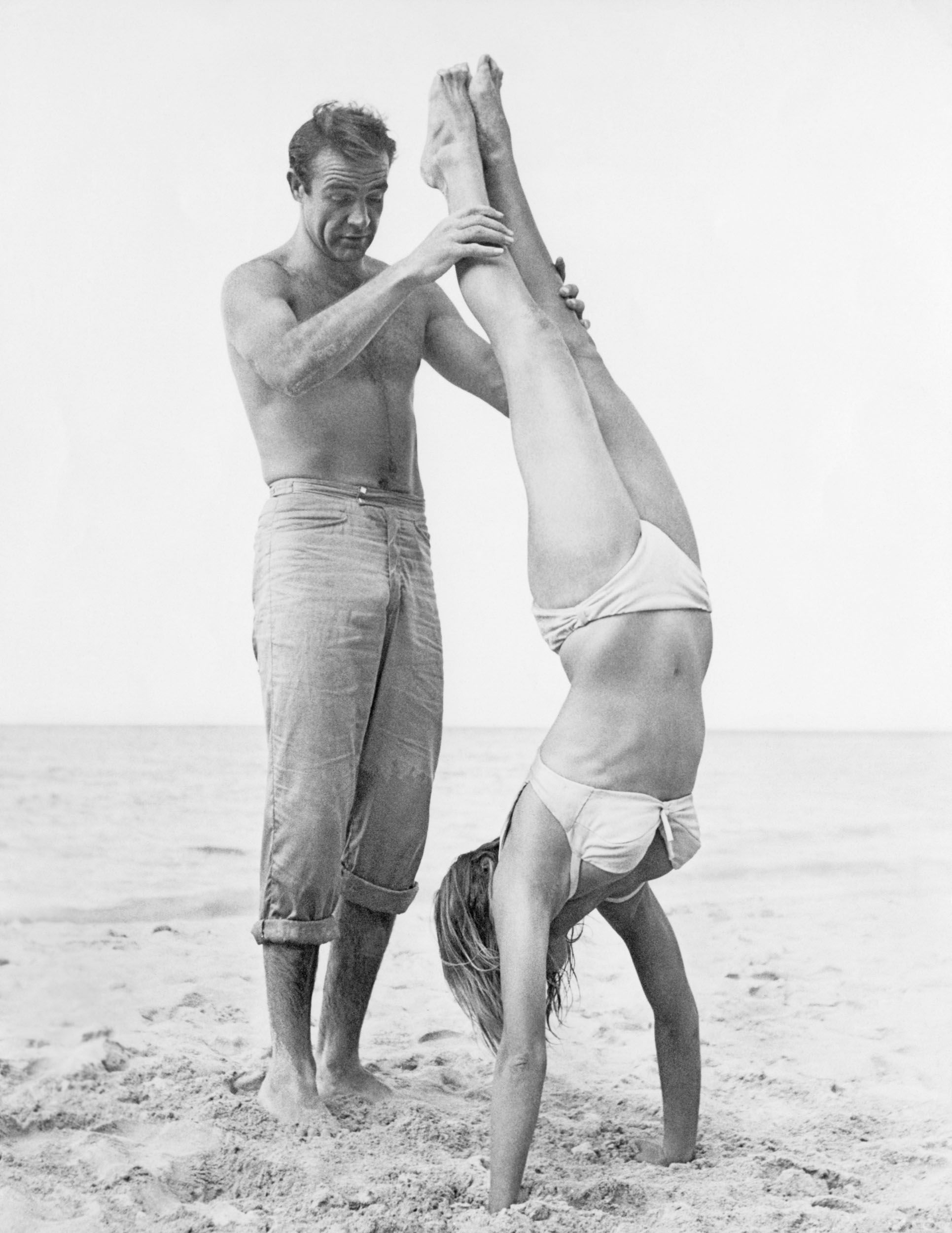 Sean Connery holds Ursula Andress while she does a handstand on a beach in a white bikini on the set of the film Dr. No .