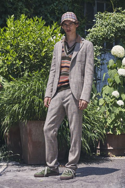 Standing, Botany, Street fashion, Outerwear, Tree, Plant, Suit, Shoe, Trousers,