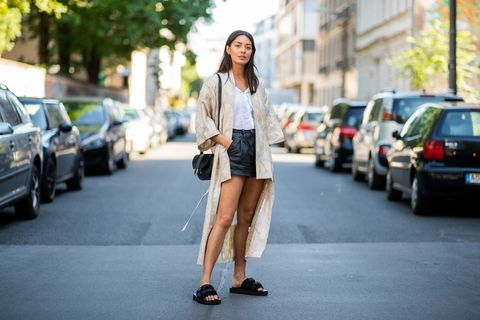 berlin, germany   june 06 model alyssa cordes wearing gestuz kimono, slip on suicoke shoes, black vintage leather shorts and white blouse, black apc bag on june 6, 2018 in berlin, germany photo by christian vieriggetty images