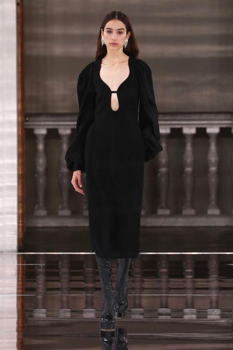 Fashion model, Clothing, Fashion, Dress, Fashion show, Standing, Outerwear, Formal wear, Little black dress, Runway,