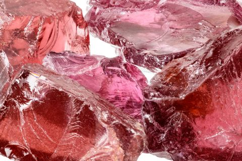 a pile of purple red rhodolite garnet gemstone crystals uncut, rough isolated on white