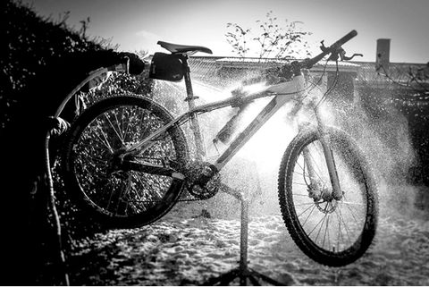 cyclist hosing down mountain bike