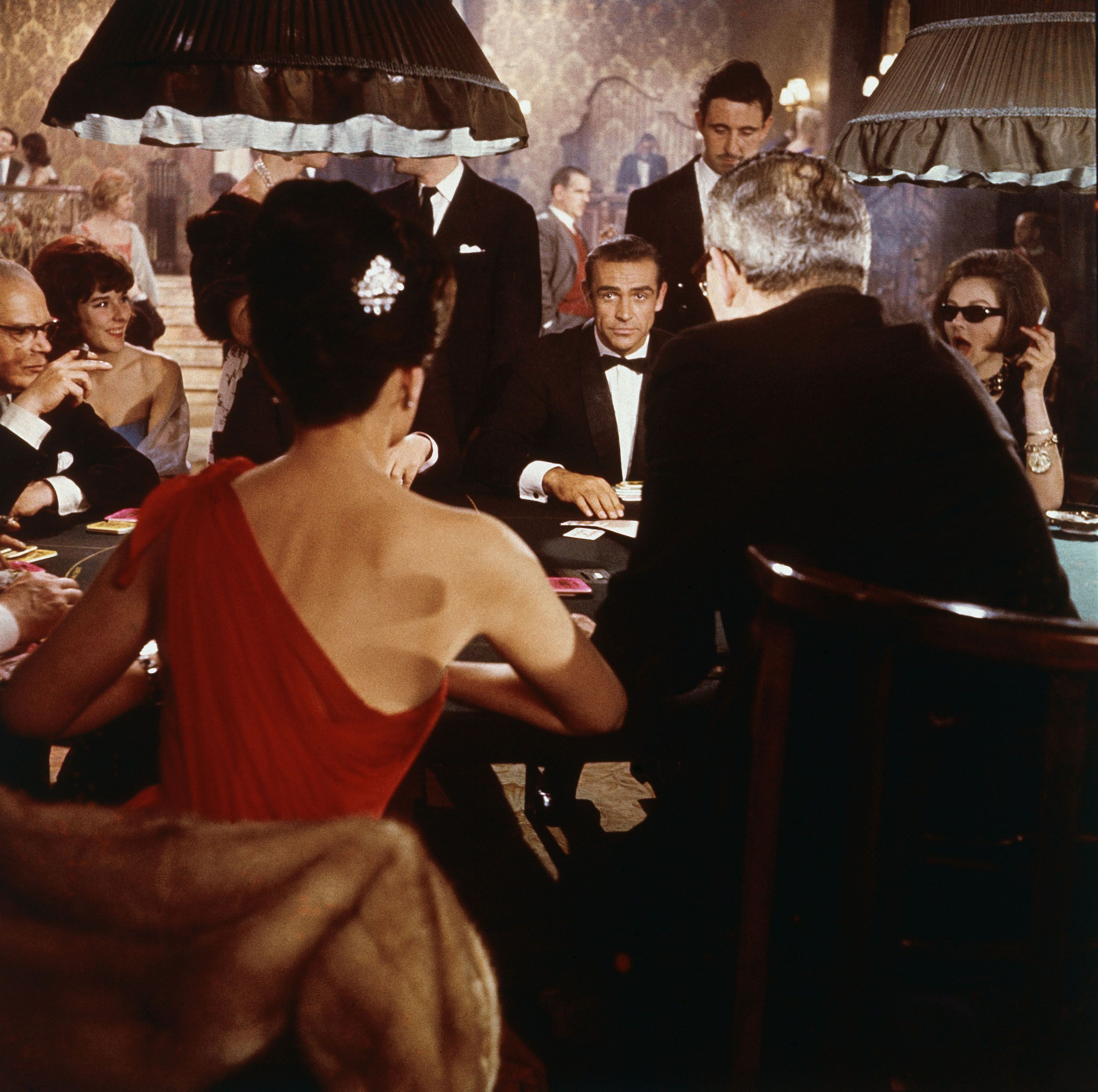 Sean Connery as James Bond sits at a casino card table in a scene from the film Dr. No.
